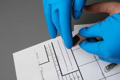 Utredare som tar fingeravtryck av misst?nkten p? tabellen Brottslig sakkunskap arkivbild