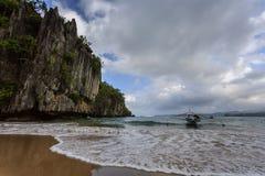 Utriggarekanoten förtöjde på stranden nära över hängande klippor i Filippinerna Royaltyfri Fotografi