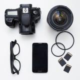 Utrustning för fotograf` s - bästa sikt av kameran, linser, kort och fotografering för bildbyråer
