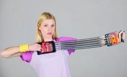 Utrustning för sport för kvinnaelasticitetsexpander med försök Hur riktig väg för bruksutrustning Öva med expanderutrustning arkivbild