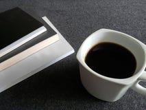 utrymme för att läsa, staplade böcker och en kaffekopp på det gråa skrivbordet fotografering för bildbyråer