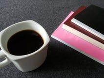 utrymme för att läsa, staplade böcker och en kaffekopp på det gråa skrivbordet arkivbild