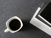 utrymme för att läsa, staplade böcker och en kaffekopp på det gråa skrivbordet arkivfoto