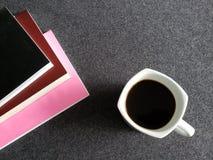 utrymme för att läsa, staplade böcker och en kaffekopp på det gråa skrivbordet royaltyfria foton