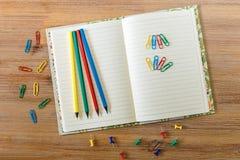 Utrymme för idérikt arbete med den öppna anmärkningsboken, blyertspennor och färgrik cli Arkivfoto