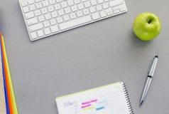 Utrymme för kontorsarbete på det gråa skrivbordet med det gröna äpplet Arkivbild