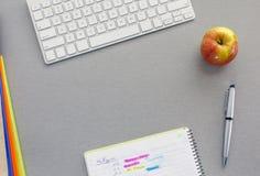 Utrymme för kontorsarbete på det gråa skrivbordet med det röda äpplet Fotografering för Bildbyråer