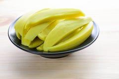 Utrzymane mangowe owoc w czarnym pucharze Zdjęcie Stock
