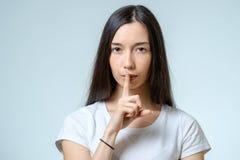 Utrzymanie cisza! Piękny młodej kobiety mienia palec na wargach obrazy stock