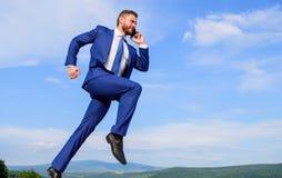 Utrzymanie iść w kierunku twój celu Biznesmena kostiumu formalny skok podczas gdy wywoławczy smartphone nieba tło Przedsiębiorca  fotografia royalty free