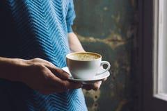 Utrzymanie w twój rękach pusta filiżanka kawy na nieociosanym tle Zdjęcie Stock