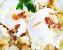Utsökta tjuvjagade ägg med olivolja, skinka, vitlök och persilja Royaltyfri Bild