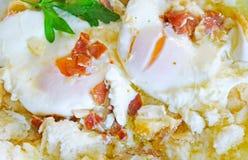 Utsökta tjuvjagade ägg med olivolja, skinka, vitlök och persilja Royaltyfria Bilder