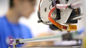 Utskrift med den plast- trådglödtråden på skrivaren 3D Tredimensionell skrivare under arbete i skolalaboratoriumet, plast- lager videofilmer