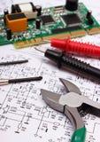 utskrivaven brädeströmkrets precisionhjälpmedel och kabel av multimeteren på diagram av elektronik Arkivfoto