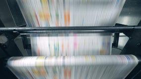 Utskrivaven tidningsrullning på en transportör, typografiska utrustningarbeten arkivfilmer