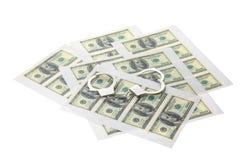 Utskrivavna ark med dollar och handbojor arkivbild