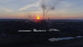 Utsläpp som luftar som surrar sikt av fabriksrör med tjock vit rök på bakgrundssolnedgång och stad stock video