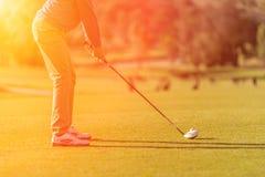 Utslagsplats för golfspelare av på solnedgången Arkivfoto