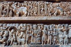 Utsmyckad baslättnad med indisk bakgrund, Lord Vishnu sammanträde, Krishna och människor i sten 12th århundradetempel, Indien Arkivbild