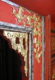 Utsmyckad guld- klippning runt om en dörröppning i Vietnam royaltyfria bilder