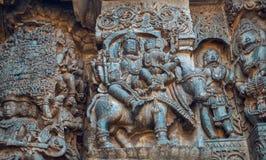 Utsmyckad lättnad av Siva och Parvathi sammanträde på tjur och pengar andra berättelser i sten 12th århundradetempel i Indien Royaltyfria Bilder