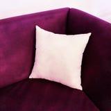 Utsmyckad purpurfärgad soffa med den vita kudden arkivfoto