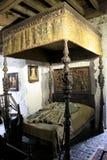 Utsmyckad säng och kläder av tiderna som visas i rum av den Bunratty slotten, Irland, nedgång, 2014 Royaltyfri Fotografi