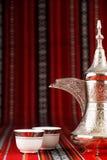 Utsmyckade arabiska tekoppar och ett dallahte lägger in Royaltyfri Foto