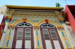 Utsmyckade dekorerade shophousefönsterslutare och wa Royaltyfri Bild