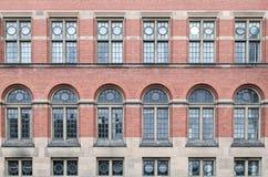 Utsmyckade fönster i en vägg för röd tegelsten arkivfoton