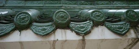 Utsmyckade krukmakeritegelplattor på taköverkant av huset arkivfoto