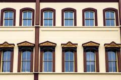 Utsmyckade Windows på gul murbrukbyggnad Arkivfoto