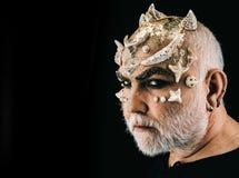Utsmyckat allhelgonaaftonsmink, skådespelare som beskriver det fula monstret med taggar på framsida Sidosikten uppsökte mannen me arkivbilder