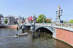 Utsmyckat forntida överbryggar med ett fartyg i Amsterdam arkivfoto