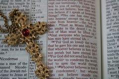 Utsmyckat guldkors på den öppna bibeln royaltyfri fotografi