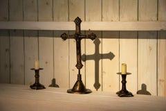 Utsmyckat kors och stearinljus på tabellen royaltyfria bilder