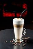 Utsmyckat lattekaffe i exponeringsglas royaltyfri bild