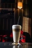 Utsmyckat lattekaffe i exponeringsglas royaltyfria foton