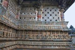 Utsmyckat perforerat fönster och dekorativa friars med gudar, dansare och andra diagram, Chennakeshava tempel Belur Karnataka arkivbilder