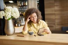 Utsmyckat skratta ung flickasammanträde på trätabellen som håller blocknote arkivfoto