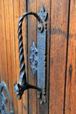 Utsmyckat svart dörrhandtag i riden ut wood dörr Royaltyfri Fotografi