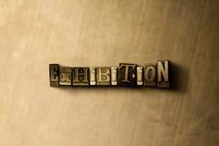 UTSTÄLLNING - närbild av det typsatta ordet för grungy tappning på metallbakgrunden arkivfoto