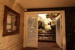 Utstående herrgård, med dörrar på havssiktskusten på solnedgången Royaltyfria Bilder