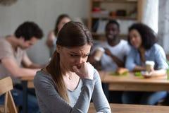 Utstött flicka som separat sitter vid andra tonåringar i kafé arkivfoto