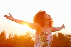 Utsträckta armar för kvinna i ett uttryck av frihet med sunflar Fotografering för Bildbyråer