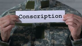 Uttagning till militärtjänstgöring som är skriftlig på papper i händer av den manliga soldaten, militärtjänst lager videofilmer