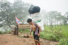 Uttaradit, Tailândia, o 5 de agosto de 2018: Trabalhador do homem forte e muita bagagem na maneira que Trekking em montanhas do ` imagens de stock royalty free