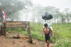Uttaradit, Tailândia, o 5 de agosto de 2018: Trabalhador do homem forte e muita bagagem na maneira que Trekking em montanhas do ` foto de stock
