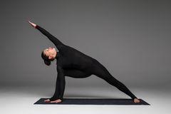 Utthita parsvakonasana. Beautiful yoga woman practice yoga poses. On grey background. Yoga concept Royalty Free Stock Photos